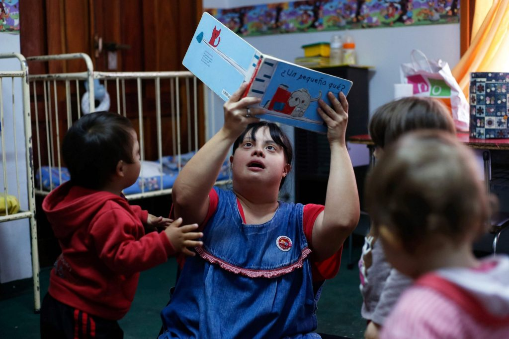 "Noelia Garella (C), a kindergarten teacher born with Down Syndrome, reads a book to children at the Jeromito kindergarten in Cordoba, Argentina on September 29, 2016. When Noelia Garella was a child, a nursery school rejected her as a ""monster."" Now 31, she is in a class of her own. In the face of prejudice, she is the first person with Down syndrome to work as a kindergarten teacher in Argentina -- and one of few in the world. / AFP PHOTO / DIEGO LIMADIEGO LIMA/AFP/Getty Images"